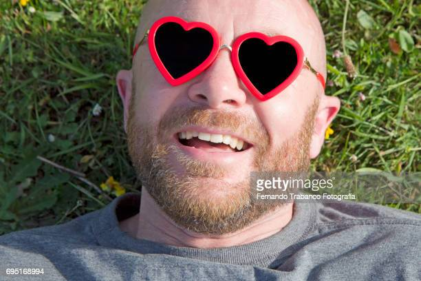 Man lying on the grass with red heart shaped sunglasses