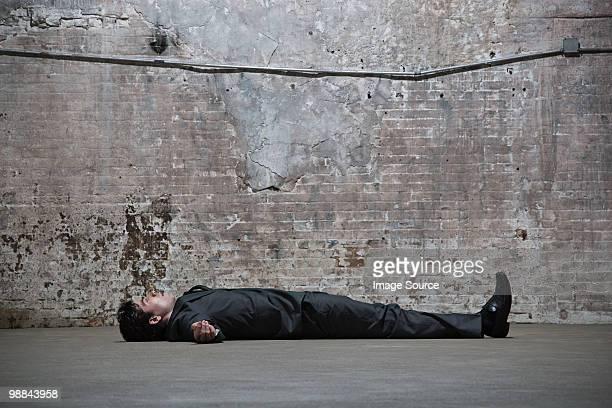 Man lying on warehouse floor