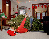 Man lying  under Cristmas tree tangled in string of lights