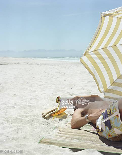 Man lying under parasol on beach