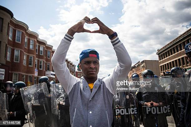 A man makes a heart shape with his hands during a protest near the CVS pharmacy that was set on fire yesterday during rioting after the funeral of...