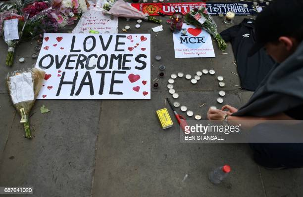 A man makes a heartshape out of candles alongside flowers and messages in Albert Square in Manchester northwest England on May 24 placed in tribute...