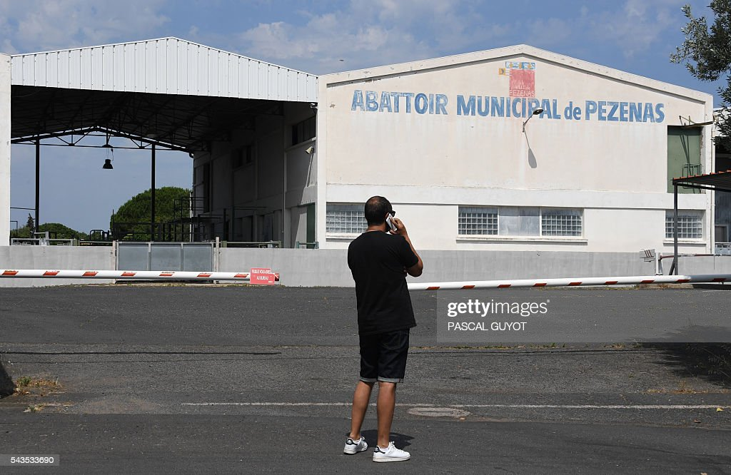 A man makes a phone call in front of the municipal slaughterhouse of Pezenas, on June 29, 2016 after the L214 association released a video denouncing poor animal handling methods in two southern France's slaughterhouses in Pezenas and Puget-Theniers. GUYOT