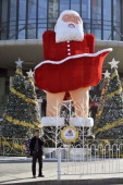 A man makes a phone call near a blowup Santa Claus doll that imitates the famous Marilyn Monroe pose before a shopping mall in Taiyuan central...