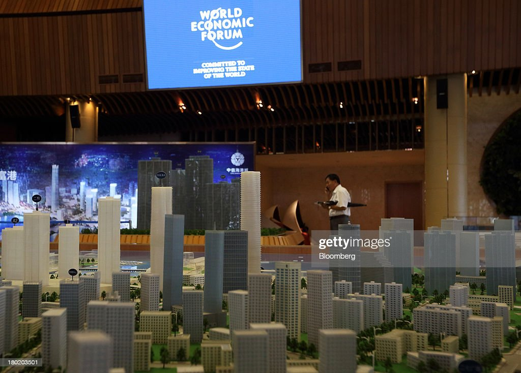 A man makes a phone call near a model of the city of Dalian at the registration point for the World Economic Forum Annual Meeting of The New Champions 2013 in Dalian, China, on Tuesday, Sept. 10, 2013. The World Economic Forum Annual Meeting Of The New Champions 2013 will be held in Dalian from Sept. 11 to 13. Photographer: Tomohiro Ohsumi/Bloomberg via Getty Images