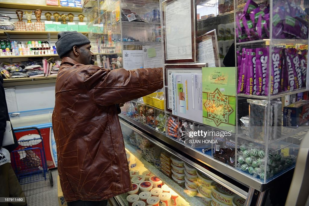 A man makes a purchase in the OW African Market, a business that serve exiles from Guinea in the Bronx borough of New York, December 6, 2012. Nafissatou Diallo, a Guinean immigrant who accused former IMF head Dominique Strauss-Kahn of sexual assault, will agree to a settlement with Strauss-Kahn in a Bronx court on December 10. AFP PHOTO/Stan HONDA