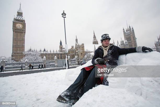 A man makes an armchair out of snow in front of The Houses Of Parliament after a night of heavy snow on February 2 2009 in London England Heavy snow...
