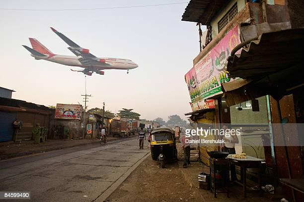 A man makes chapatis as an Air India passenger jet flies over the Jari Mari slum before landing at Mumbai Airport on February 3 2009 in Mumbai India...