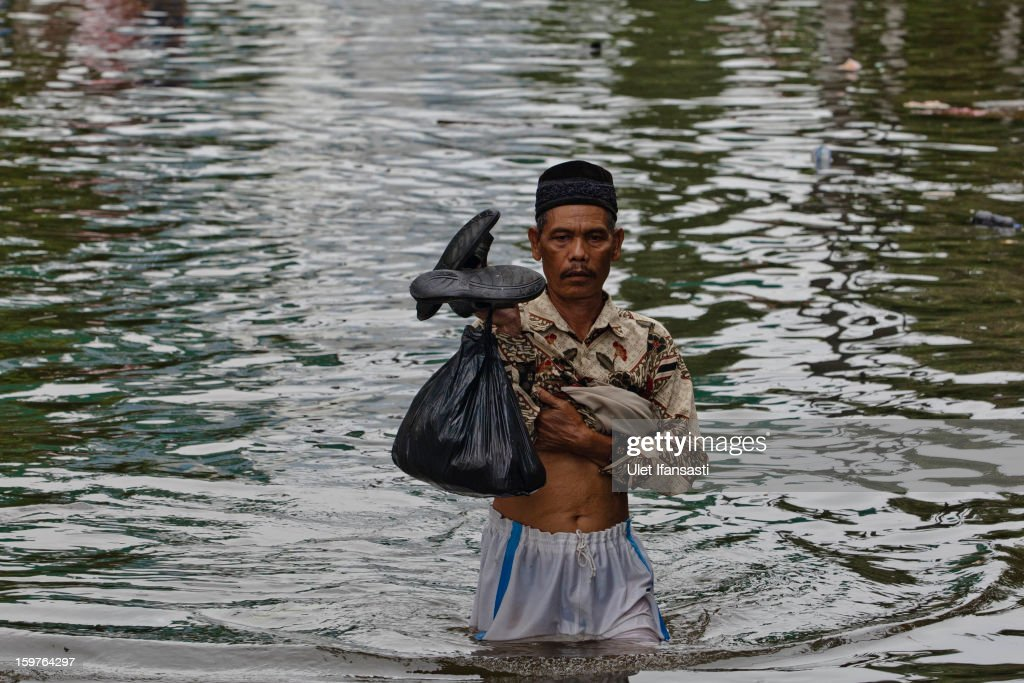 A man makes his way through floodwaters as major floods hit North Jakarta on January 20, 2013 in Jakarta, Indonesia. The death toll has risen to at least 21 since severe flooding struck the city on January 17. The US has offrered US$150,000 (Rp 1.44 billion) in aid.