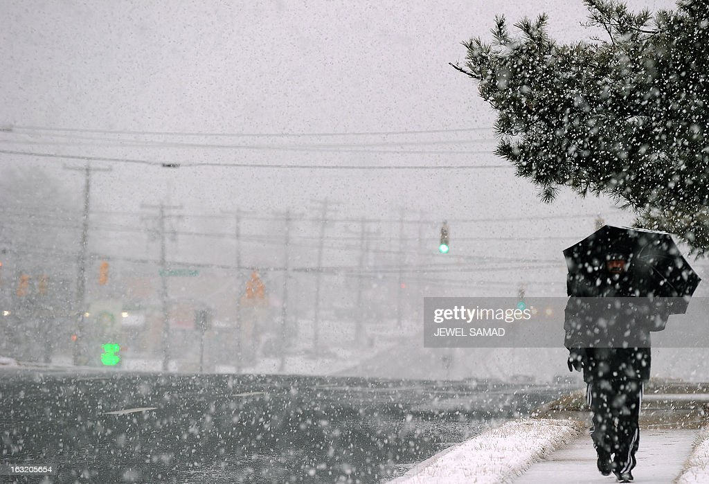 A man makes his way under a heavy snowfall in Silver Spring, Maryland, on March 6, 2013. A massive winter storm pounding the northern US on March 6, grounded 2,600 flights, closed hundreds of schools and made roadways and highways impassible. At least four people were reportedly killed in accidents on icy and snow covered roads and highways. AFP PHOTO/Jewel Samad