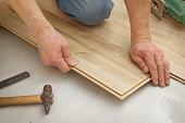 Man makes laying laminated panels, simulating light oak