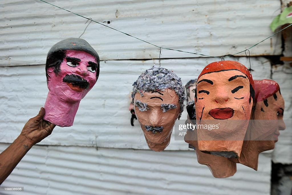 A man makes 'Old Year' dolls in Cali, Colombia, on December 31, 2012. It is a popular tradition in Colombia to burn 'Old Year' dolls (made of cardboard, sawdust and cloth and which represent the bad things of the year that goes) on the last night of the year. AFP PHOTO/Luis ROBAYO