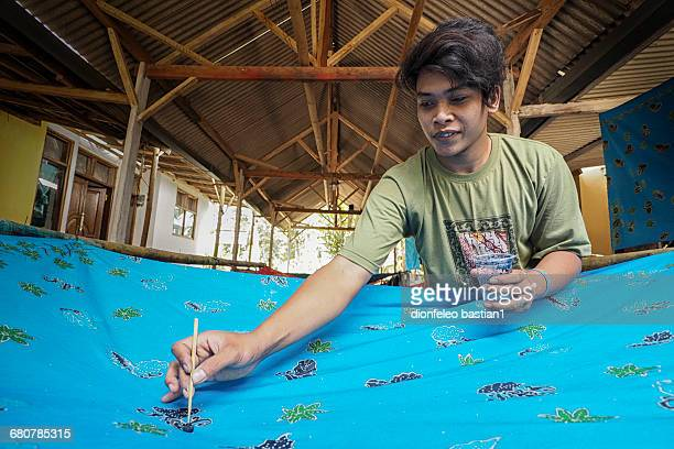 Man making a batik by brushing hot wax on cloth, Jember, East Java, Indonesia