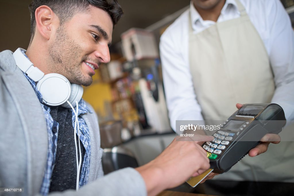 Man making a credit card payment at a cafe