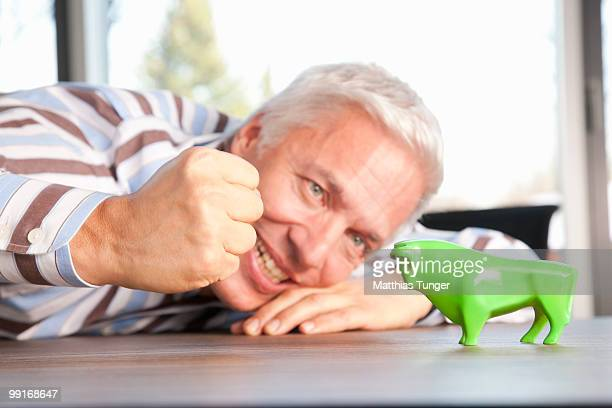 Man making a fist towards a green bull