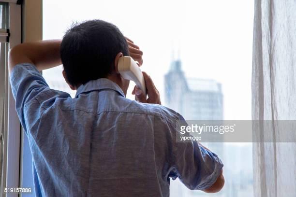 Homme fait un appel téléphonique à côté de la fenêtre