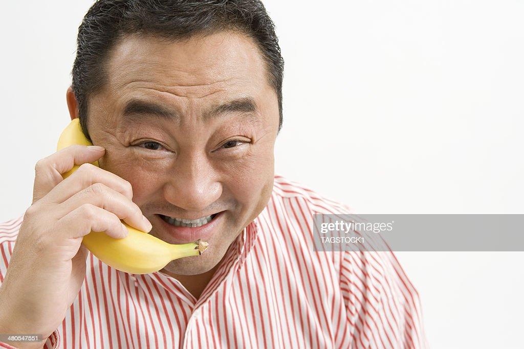 Man making a phone call using banana : Stock Photo