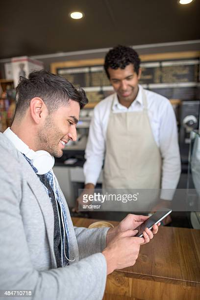 Man making a smart payment at a cafe