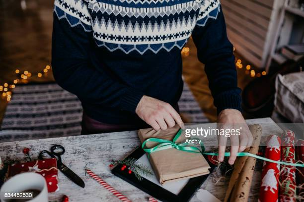 Man making bow on the Christmas gift