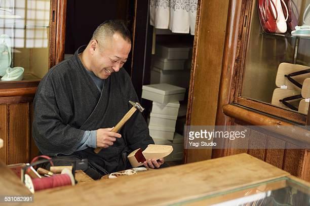 Man making clogs in his geta store