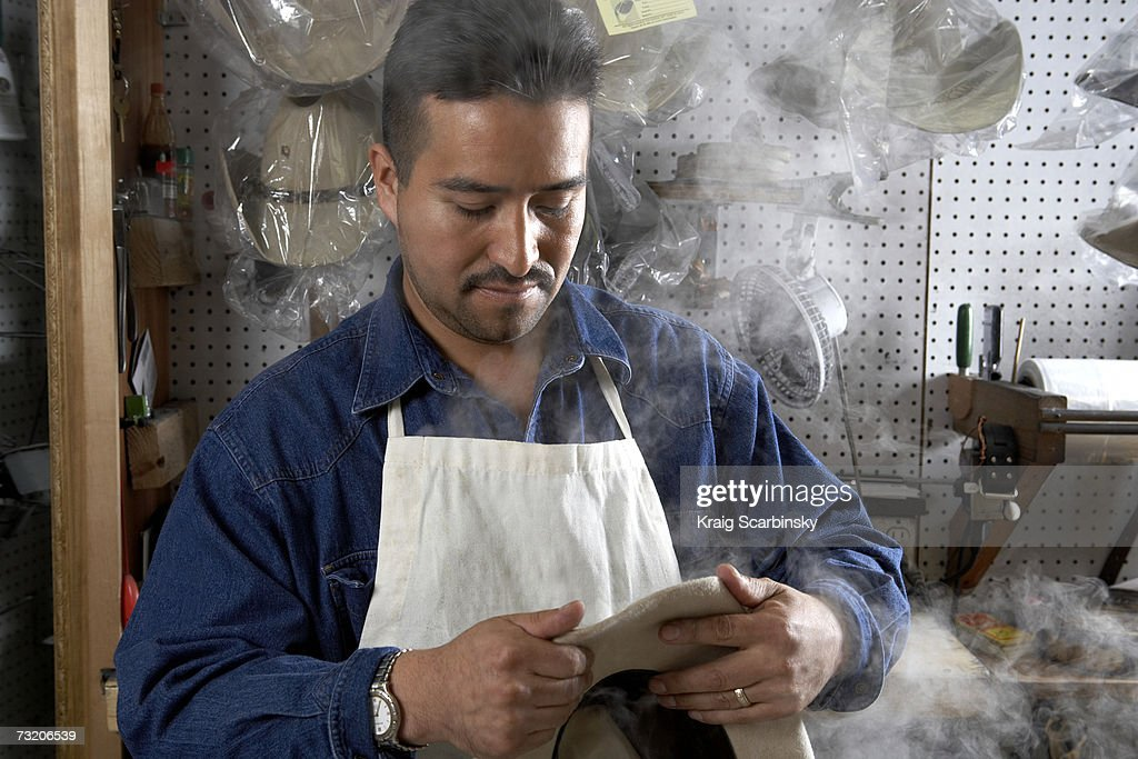 Man making cowboy hats in store : Stock Photo