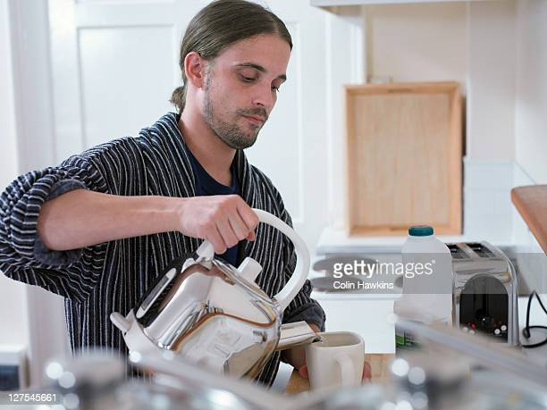 Man making cup of tea in kitchen