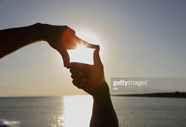 Man making finger frame against the sky at dusk
