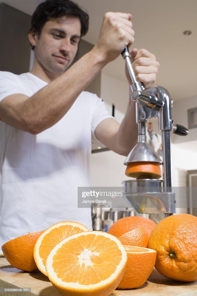 Man making fresh orange juice : Stock Photo