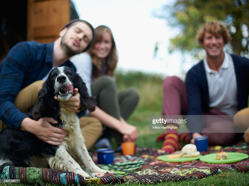 Man making fuss of dog outside yurt. : Stock Photo