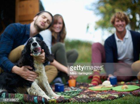 Man making fuss of dog outside yurt. : Stock Photo