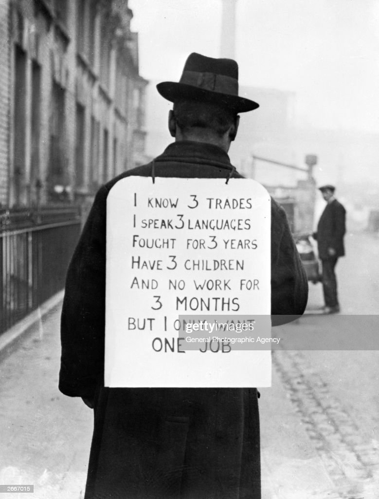 A man making his own protest against unemployment. The sign on his back reads: 'I know 3 trades, I speak 3 languages, fought 3 years, have 3 children and no work for 3 months, but I only want one job.'