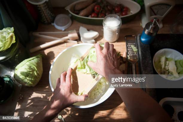 Man making home fermented sauerkraut: grating cabbage