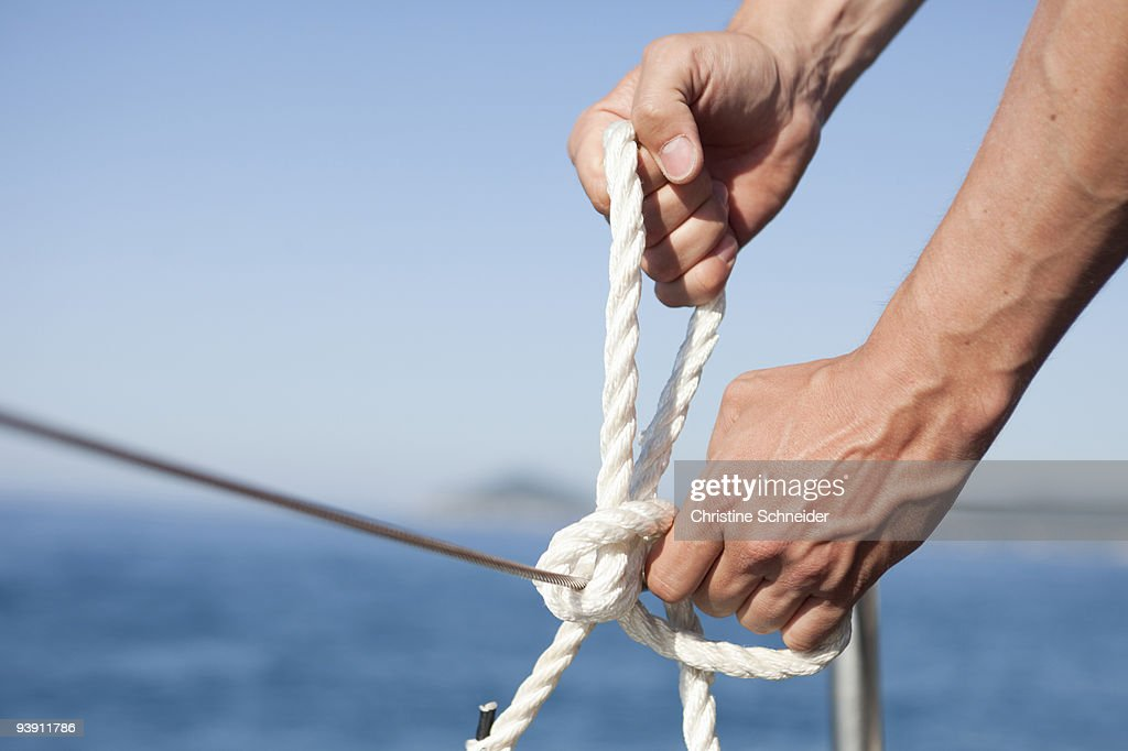 man making knot into rope