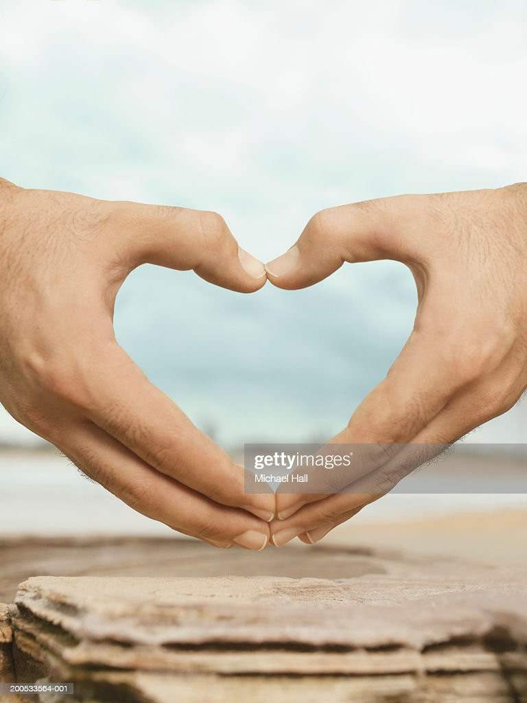 Man making love heart shape with hands, close-up : Stock Photo