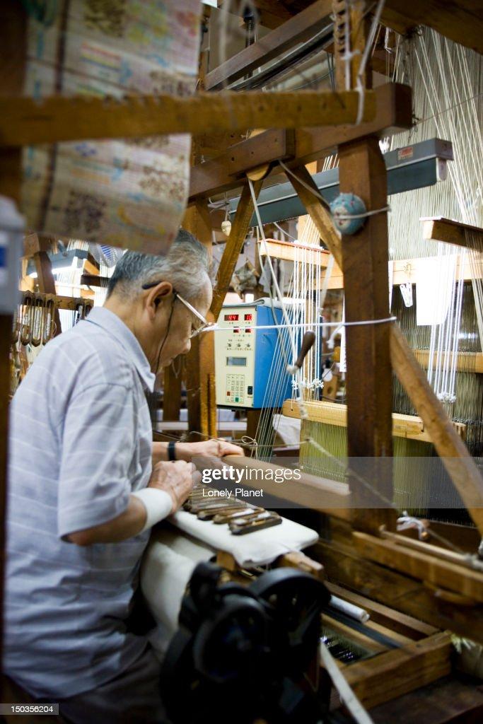 Man making obi (a silk sash to hold kimono) on a hand loom. : Stock Photo