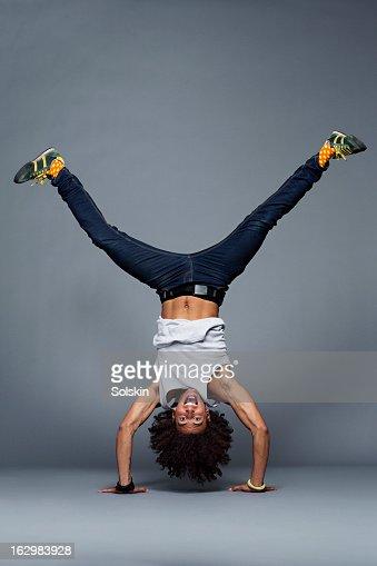 Man making one arm handstand, studio background : Stock Photo