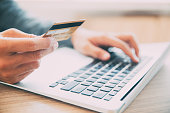 Close-up of male hands holding credit or debit card and entering information on laptop. Businessman making online purchase with credit card