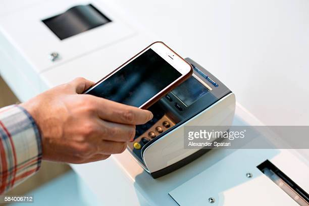 Man making purchases through mobile payment with his smartphone and terminal