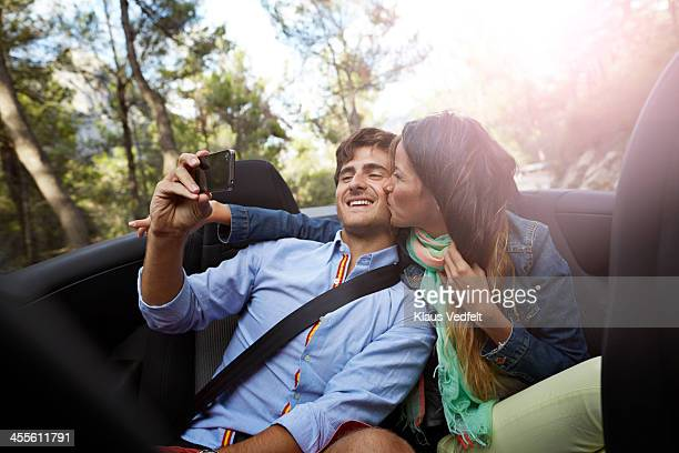 Man making selfie, while girlfriend kissing him