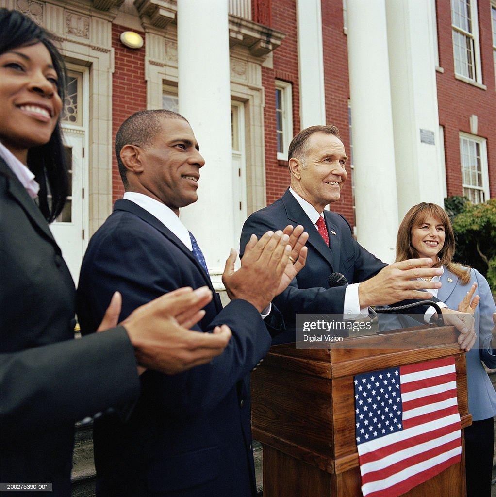 Man making speech at podium outside building, associates applauding : Stock Photo