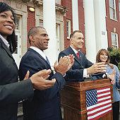 Man making speech at podium outside building, associates applauding