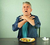 A man is panicking and is in trouble as he chokes on food and is making the official international sign for 'I'm choking' by placing his hands around his neck with outstretched fingers.