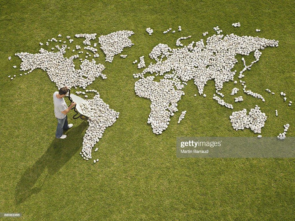 Man making world map made of rocks : Stock Photo