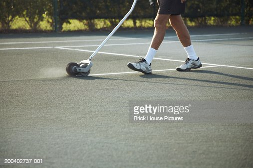Man marking lines on tennis court, low section : Stock Photo