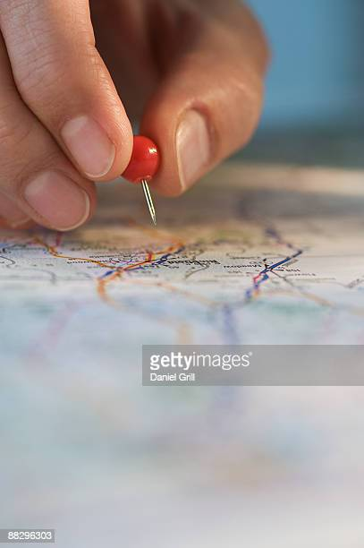 Man marking location on map