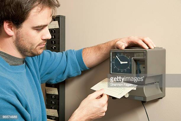 A man marking payroll record with time clock