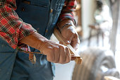 A man is measuring a stick of wood. He's wearing a flannel shirt and a safety suit. The photo is a close-up of his hands.