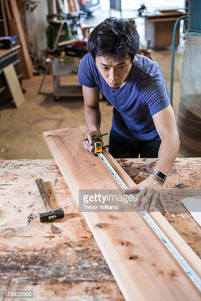 A man measuring and marking a piece of wood