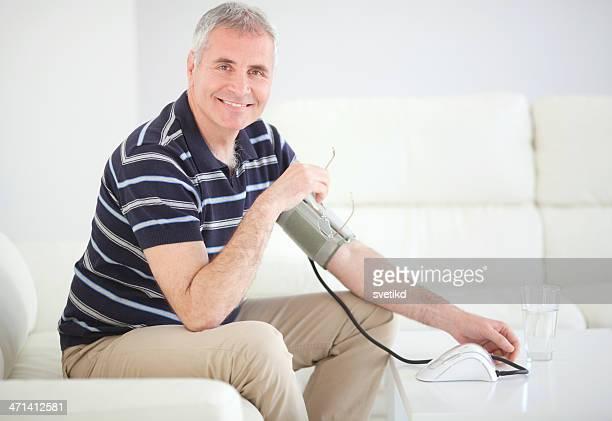Uomo di misurare la pressione arteriosa a casa.