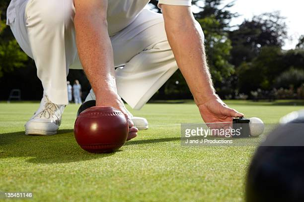 Man measuring bowls on a bowling green